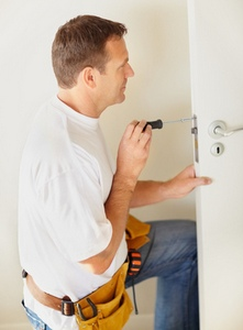 Middle aged carpenter fixing a lock in the door